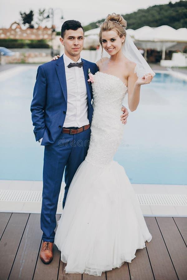 时髦的愉快的摆在水池大海的新娘和新郎在结婚宴会在餐馆 新婚佳偶华美的婚姻的夫妇  免版税库存图片