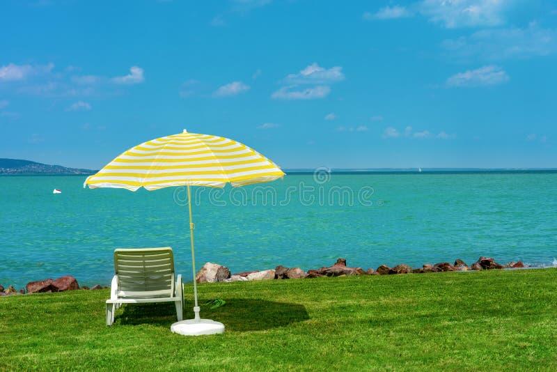 时髦的懒人塑料sunbed与在绿草的黄色条纹遮光罩沙滩伞在海滩在夏天在露天下 免版税图库摄影