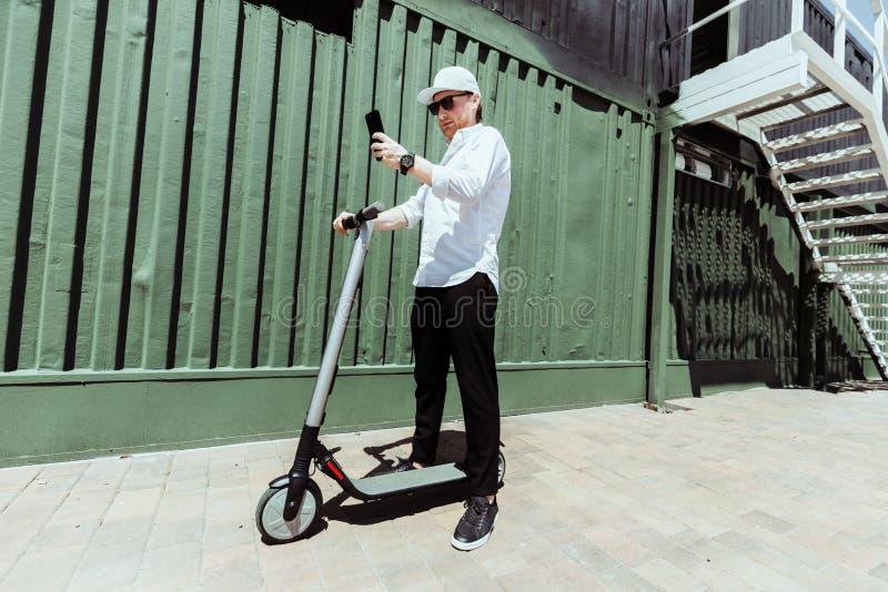 时髦的成套装备的时髦人士使用他的智能手机,当站立在有电滑行车的时街道 库存图片