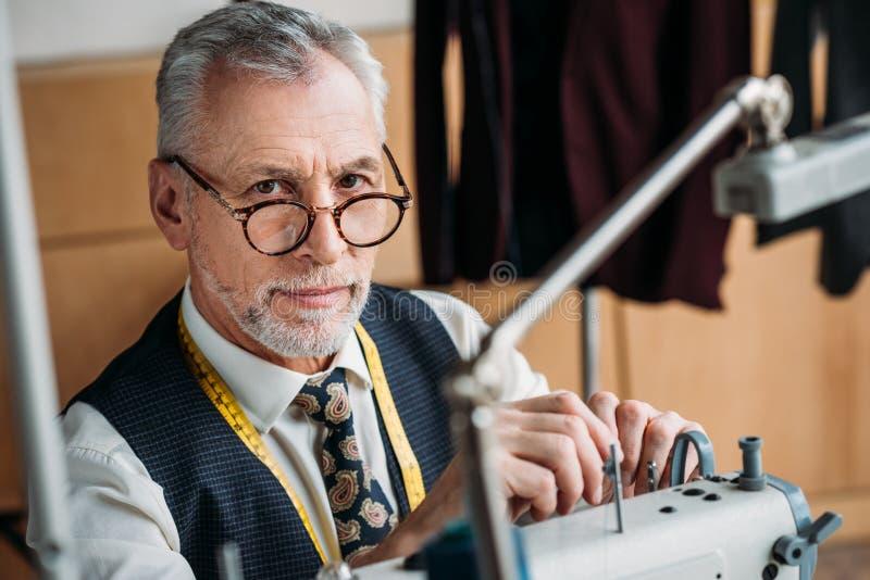 时髦的成熟裁缝与缝纫机一起使用在车间和看 免版税图库摄影