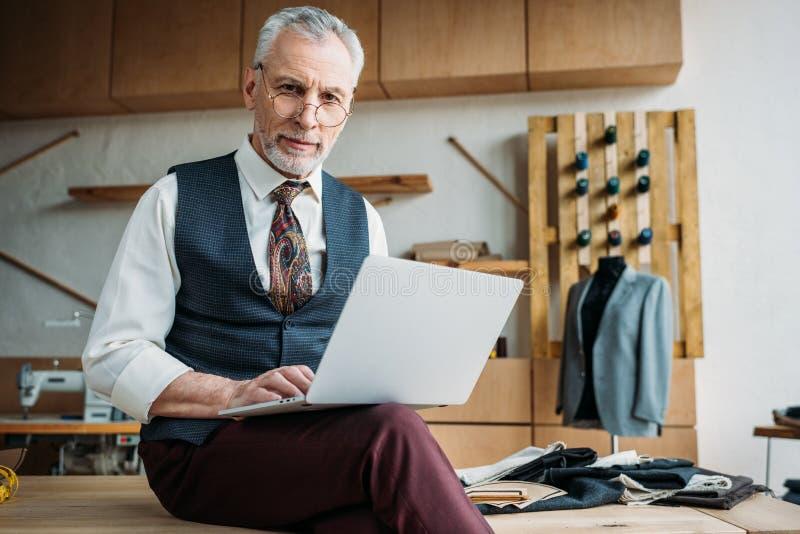 时髦的成熟裁缝与膝上型计算机一起使用,当坐桌时 库存图片