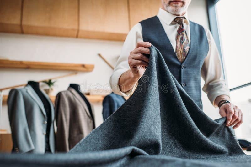 时髦的成熟裁缝播种的射击有灰色布料的 免版税图库摄影