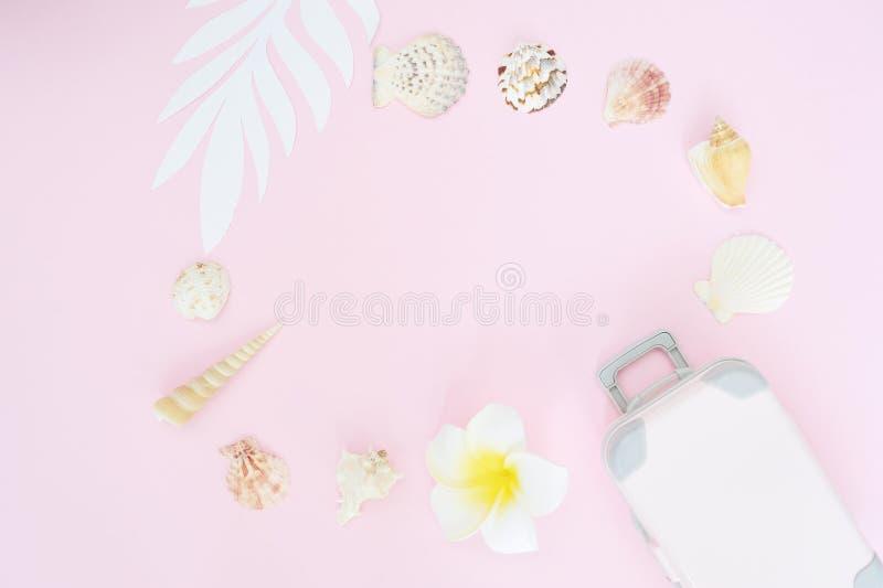 时髦的手提箱、白花和贝壳在桃红色背景,顶视图 E 旅行的概念 库存照片