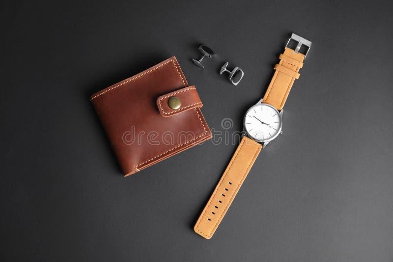 时髦的手表、袖扣和钱包在黑背景 免版税库存图片
