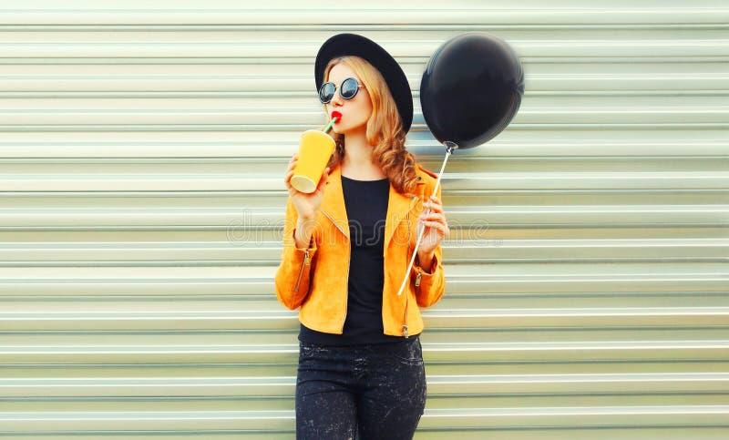 时髦的拿着黑气球的妇女饮用的果汁 免版税图库摄影