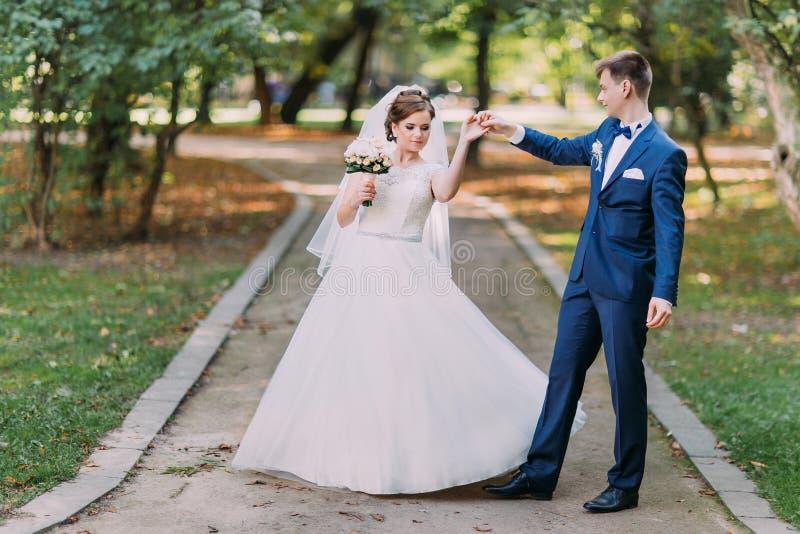 时髦的新婚佳偶夫妇的舞蹈在晴朗的公园 免版税库存图片