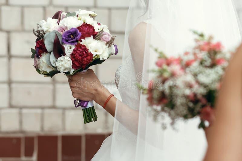 时髦的新郎和新娘有土气花束的,女傧相有pi的 免版税库存照片
