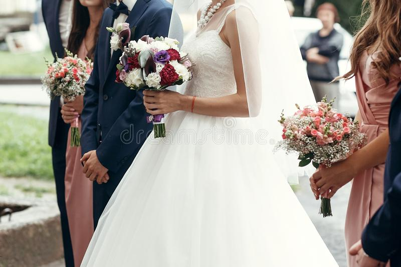 时髦的新郎和新娘有土气花束的,女傧相有pi的 库存图片