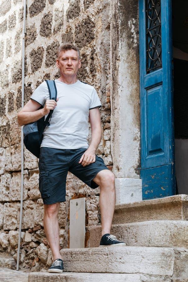 时髦的旅游人在一件白色衬衣和短裤穿戴了与背包在他的肩膀 站立在步欧洲城市 免版税库存照片