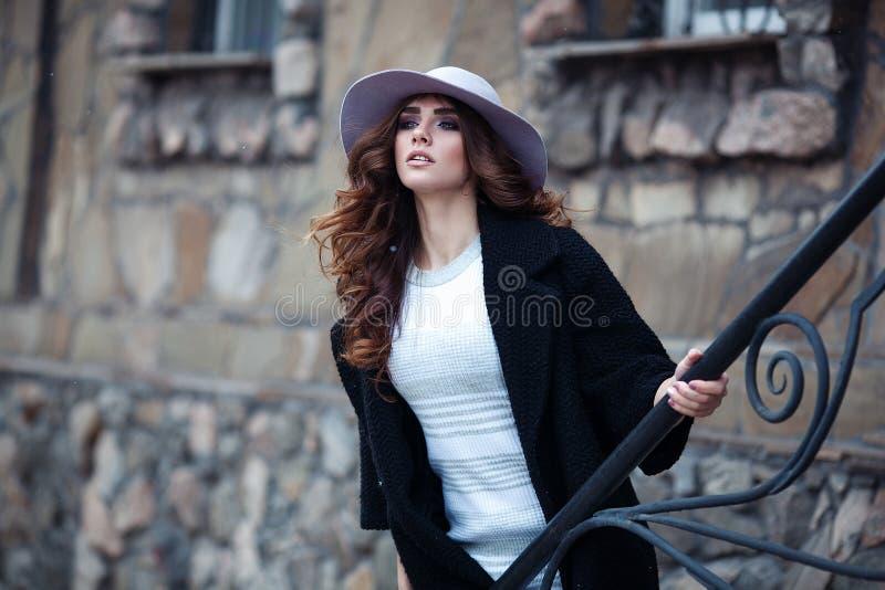 时髦的时髦黑外套和帽子ove的美丽的端庄的妇女 免版税库存照片