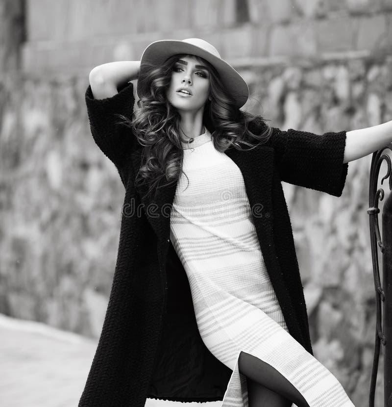 时髦的时髦黑外套和帽子ove的美丽的端庄的妇女 库存图片