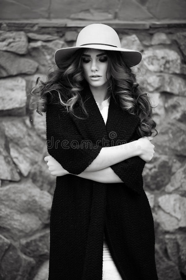 时髦的时髦黑外套和帽子ove的美丽的端庄的妇女 图库摄影