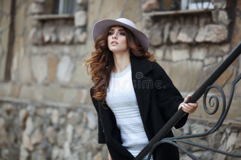 时髦的时髦黑外套和帽子ove的美丽的端庄的妇女 免版税库存图片