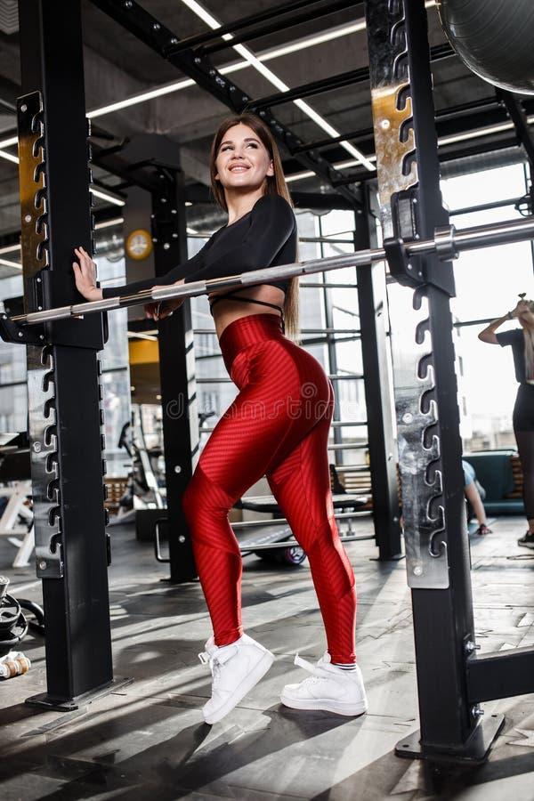 时髦的明亮的体育衣裳的美丽的苗条女孩在现代健身房的单杠旁边做姿势 图库摄影