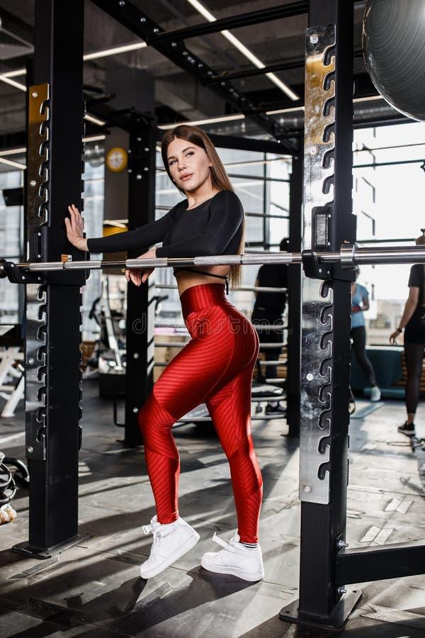 时髦的明亮的体育衣裳的美丽的苗条女孩在现代健身房的单杠旁边做姿势 免版税图库摄影