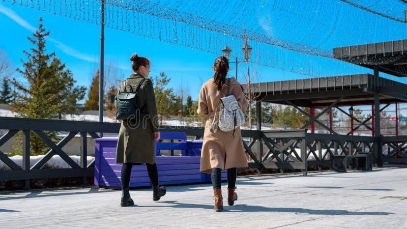 时髦的春天外套和背包的两名妇女在喀山的城市堤防走 底下背面图 免版税库存照片