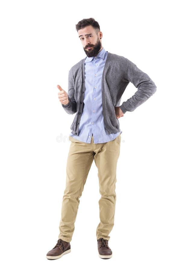时髦的有胡子的聪明的偶然显示赞许姿态和神色的人佩带的羊毛衫在照相机 库存照片