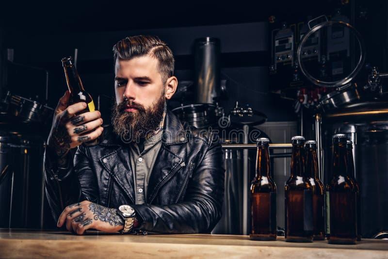 时髦的有胡子的骑自行车的人在制片者啤酒厂穿戴了坐在酒吧柜台的黑皮夹克 免版税库存图片
