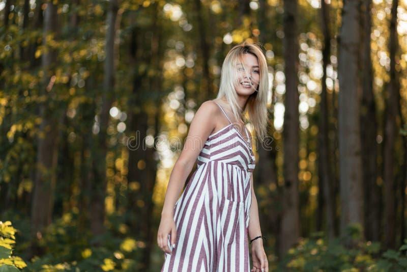 时髦的桃红色镶边sundress步行的俏丽的滑稽的年轻白肤金发的妇女在树中的森林在一个明亮的晴朗的夏日 库存照片