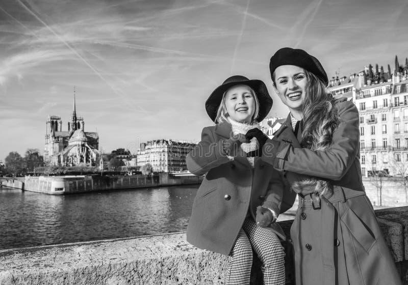 时髦的母亲和女儿在显示心形的手的巴黎 免版税库存照片