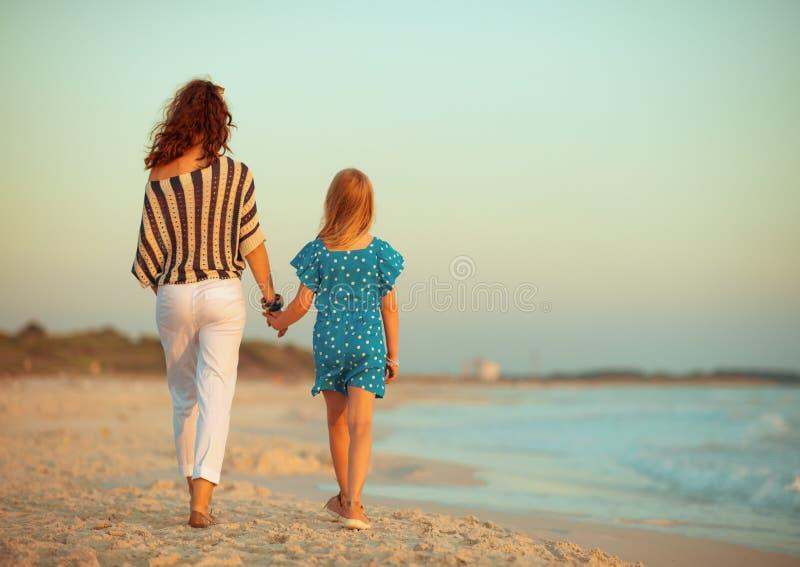 时髦的母亲和女儿海岸的在晚上走 免版税库存图片