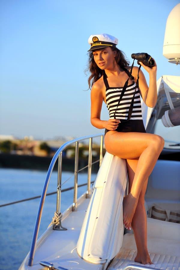 时髦的泳装和上尉帽子的妇女在私有快艇在度假 库存图片