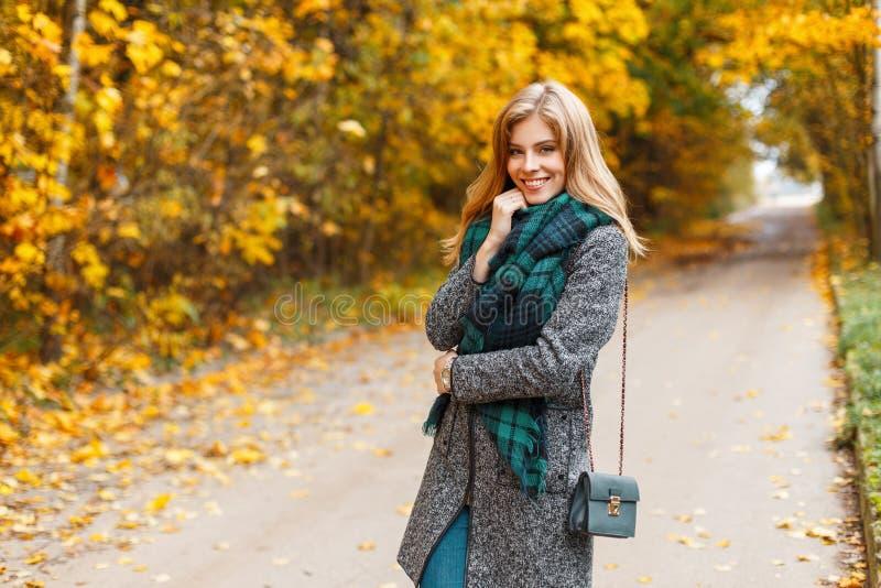 时髦的温暖的季节性衣裳的快乐的俏丽的年轻愉快的妇女有一个皮革提包的是站立和微笑在路 库存图片