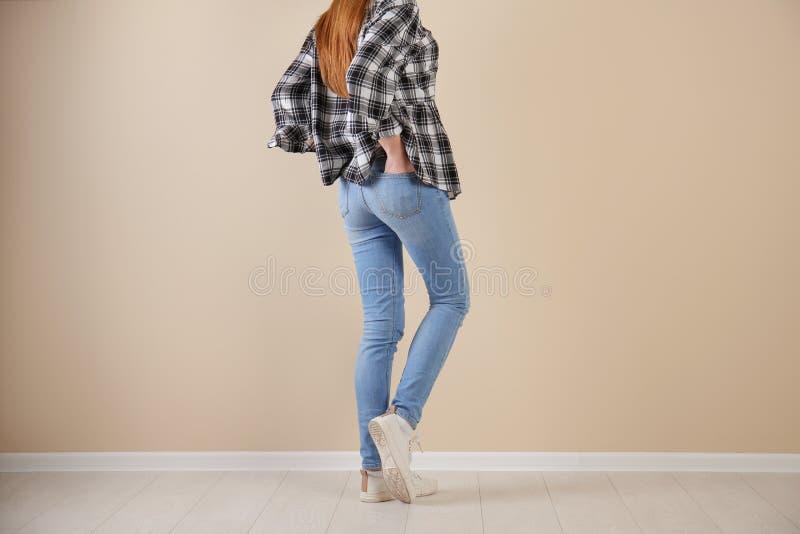 时髦的牛仔裤的少妇临近墙壁 免版税图库摄影