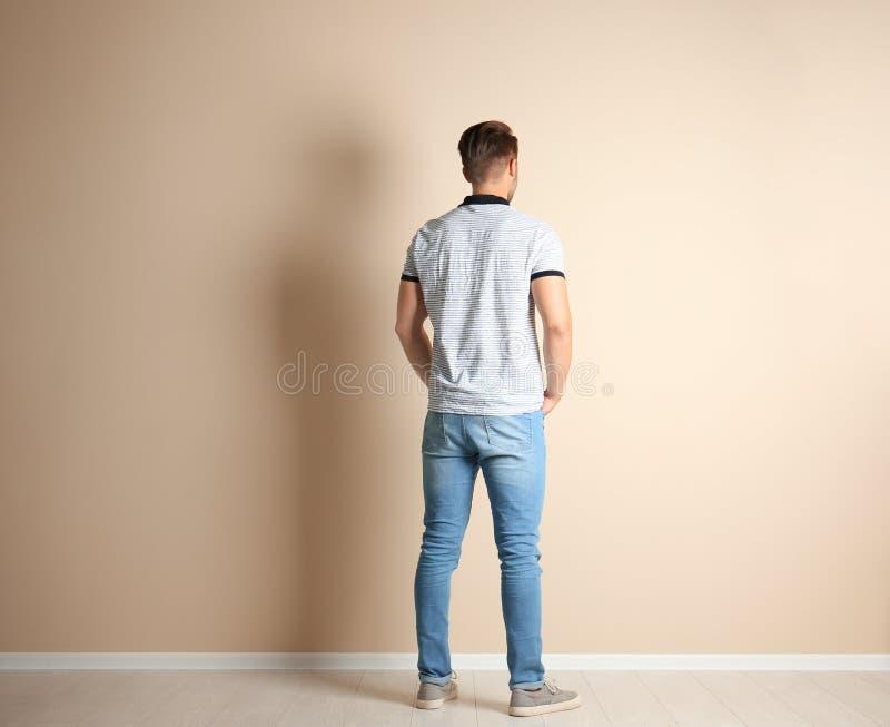 时髦的牛仔裤的年轻人临近墙壁 免版税图库摄影