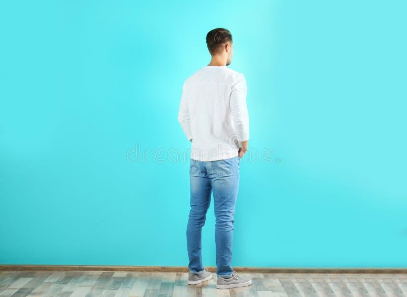 时髦的牛仔裤的年轻人临近墙壁 图库摄影