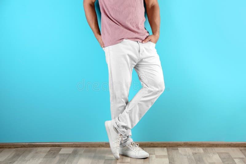 时髦的牛仔裤的年轻人临近颜色墙壁, 免版税图库摄影