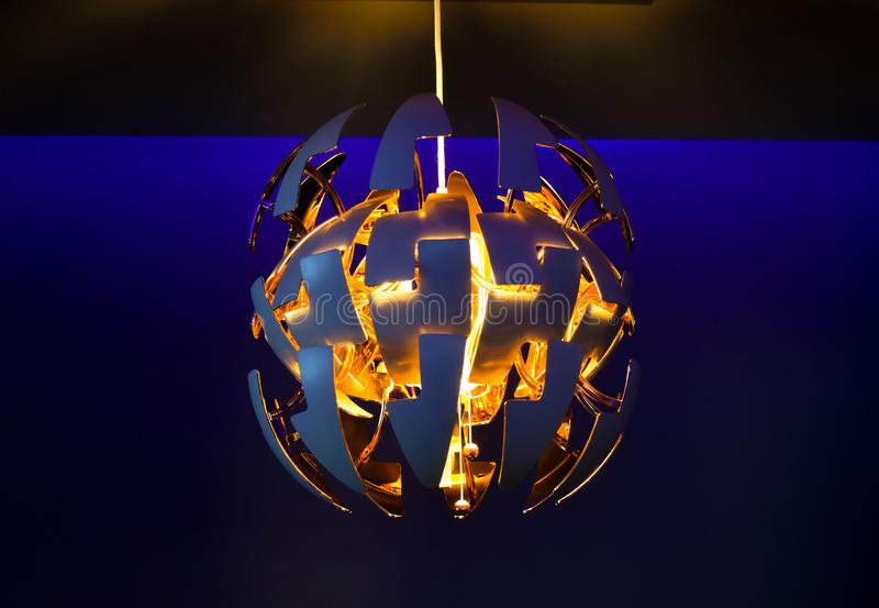时髦的现代枝形吊灯在蓝色屋子做光 免版税图库摄影