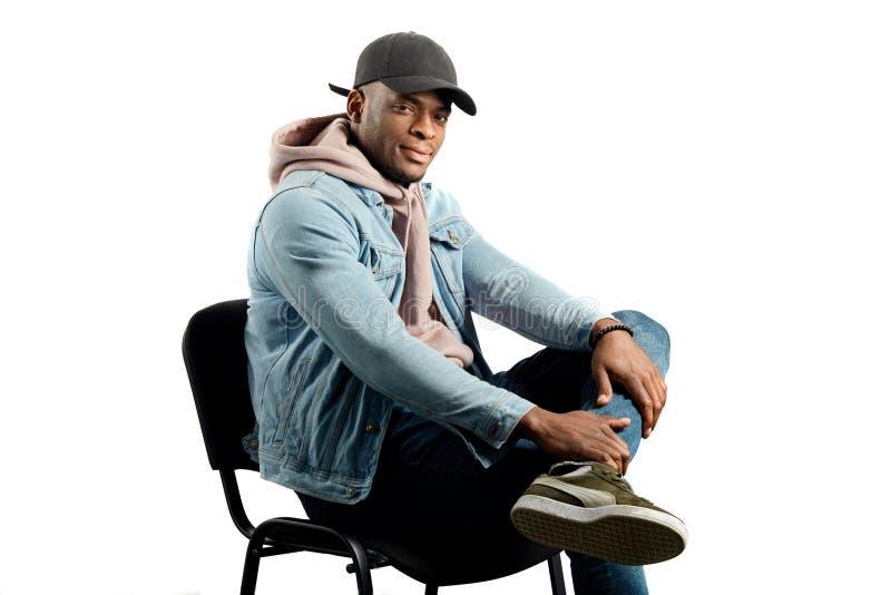 时髦的男性模型坐椅子在演播室 免版税图库摄影