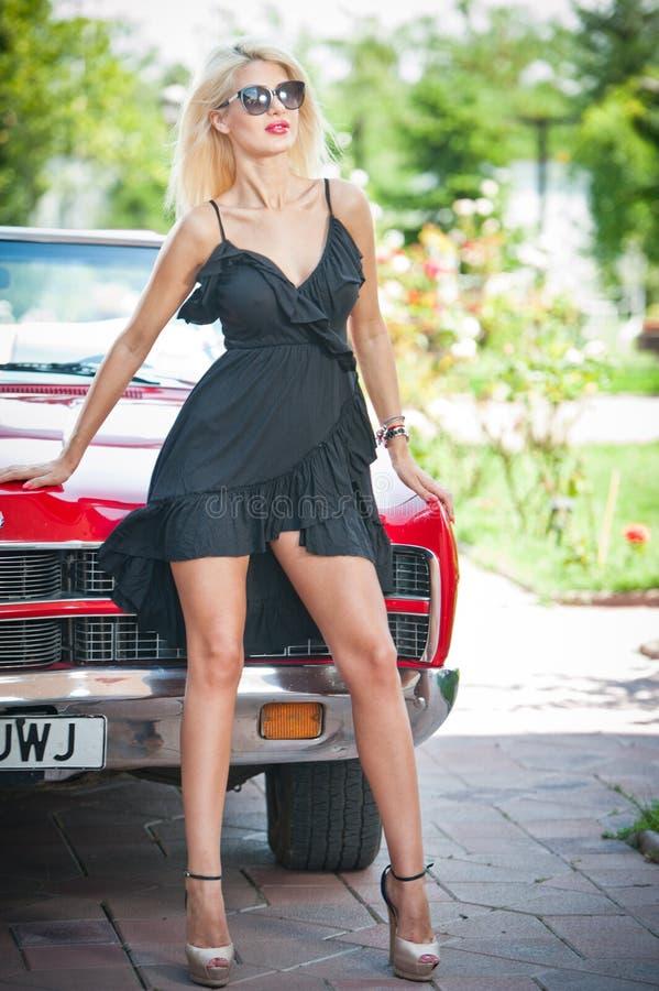 时髦的白肤金发的葡萄酒妇女夏天画象有摆在红色减速火箭的汽车附近的长的腿的 时兴的可爱的公平的头发女性 库存图片