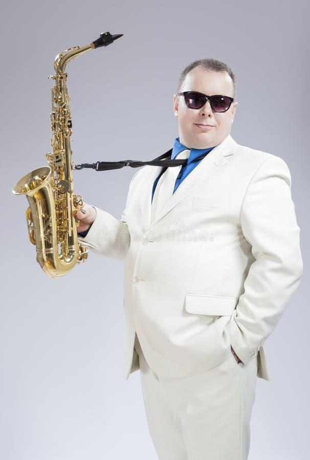 时髦的白色衣服和太阳镜的男性Saxo球员 免版税库存照片
