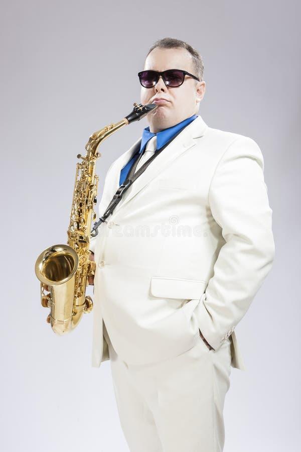时髦的白色衣服的英俊的男性Saxo摆在反对白色的球员和太阳镜 库存图片
