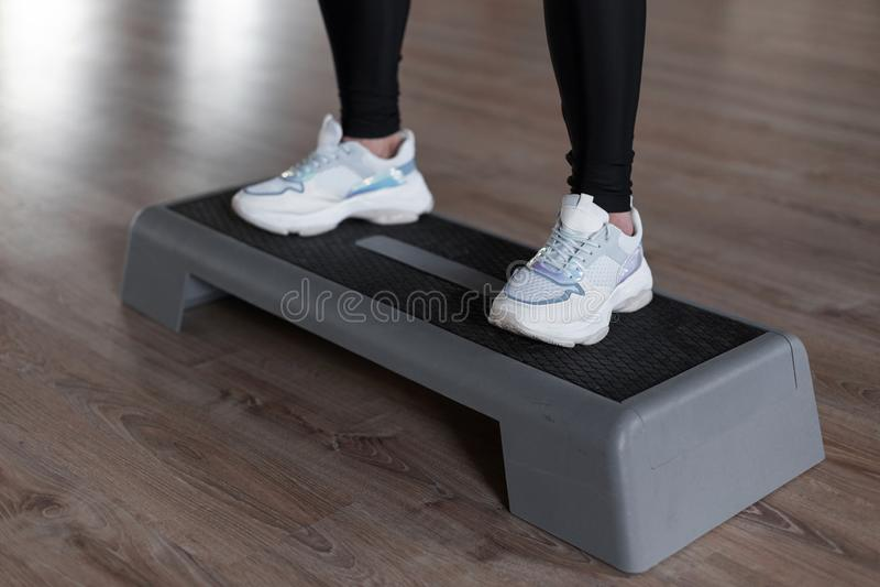 时髦的白色运动鞋的运动的年轻女人在绑腿在健身房的平台步蹲下 做早晨运动的女孩 免版税图库摄影