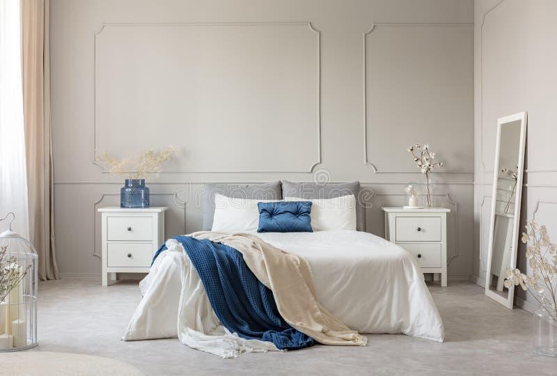 时髦的白色,灰色和汽油蓝色卧室设计,在空的墙壁上的拷贝空间 免版税库存图片