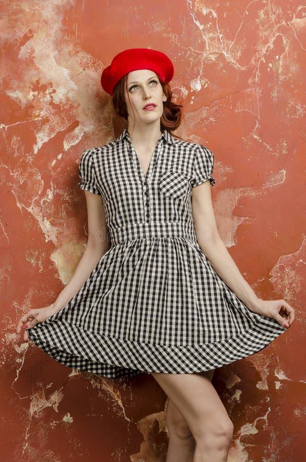 时髦的礼服的年轻时髦的妇女在葡萄酒样式和一顶红色贝雷帽 免版税图库摄影