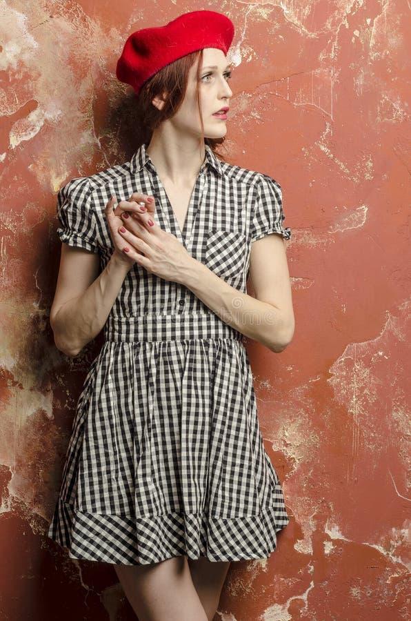 时髦的礼服的年轻时髦的妇女在葡萄酒样式和一顶红色贝雷帽 库存图片