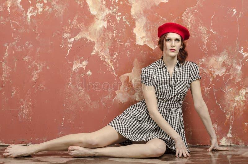 时髦的礼服的年轻时髦的妇女在葡萄酒样式和一顶红色贝雷帽 库存照片
