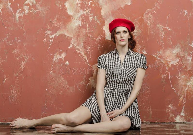 时髦的礼服的年轻时髦的妇女在葡萄酒样式和一顶红色贝雷帽 免版税库存照片