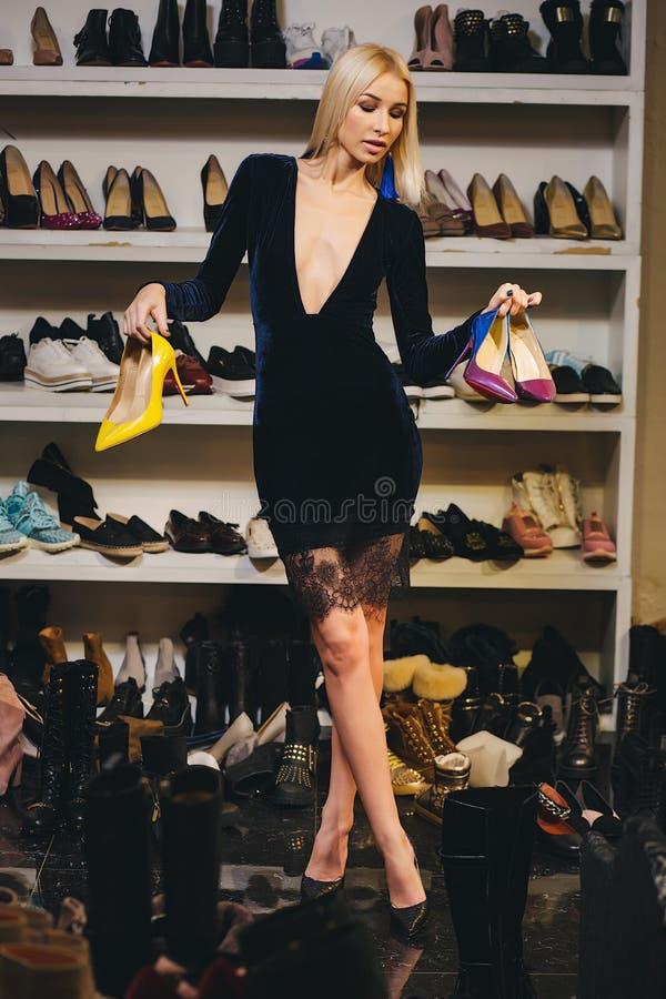 时髦的礼服的年轻白肤金发的妇女选择鞋子 免版税图库摄影