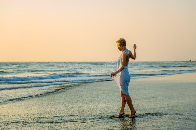 时髦的礼服立场的迷人的苗条金发碧眼的女人在海的波浪 年轻女人沿海浪赤足走并且享受休息 免版税库存照片