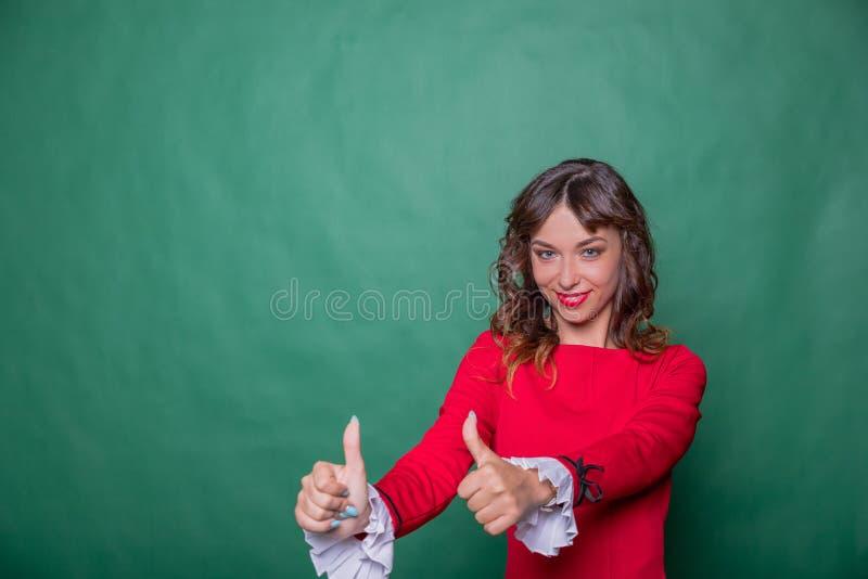时髦的红色礼服陈列赞许标志的愉快的成功的美女由两只手 查出在绿色背景 免版税图库摄影