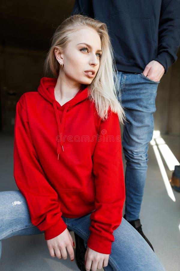 时髦的红色运动衫的现代性感的年轻白肤金发的妇女在摆在开会的牛仔裤在一个时兴的人旁边在屋子里 库存图片