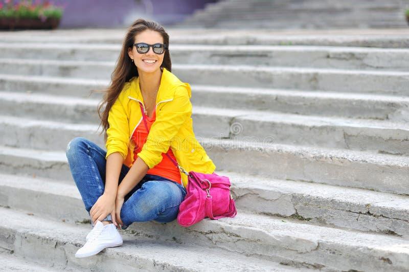 时髦的美丽的女孩坐在五颜六色的衣裳w的台阶 免版税库存图片