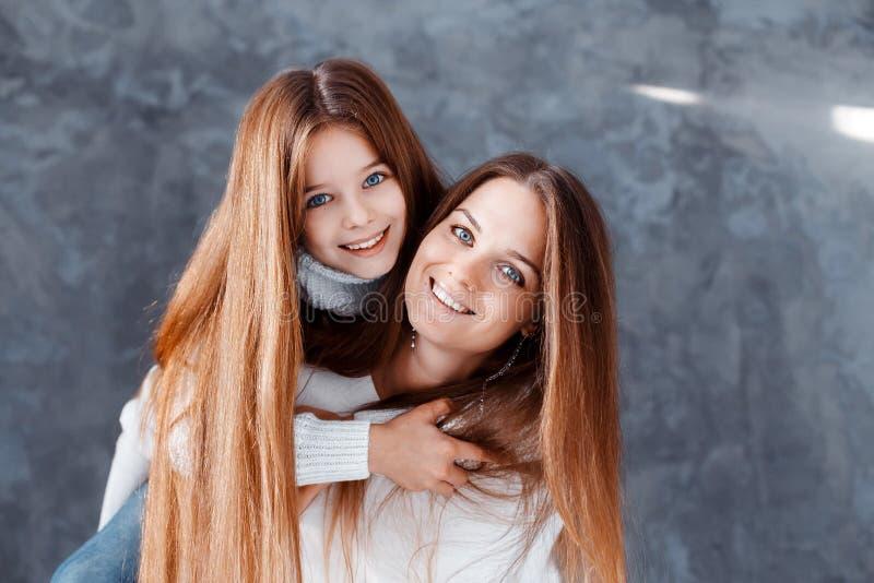 时髦的美丽的母亲和一个女儿有蓝眼睛的在获得的演播室拥抱和乐趣 家庭,爱概念 库存图片