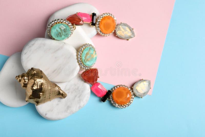 时髦的耳环、白色大理石石头和装饰壳在颜色背景 豪华首饰 免版税图库摄影