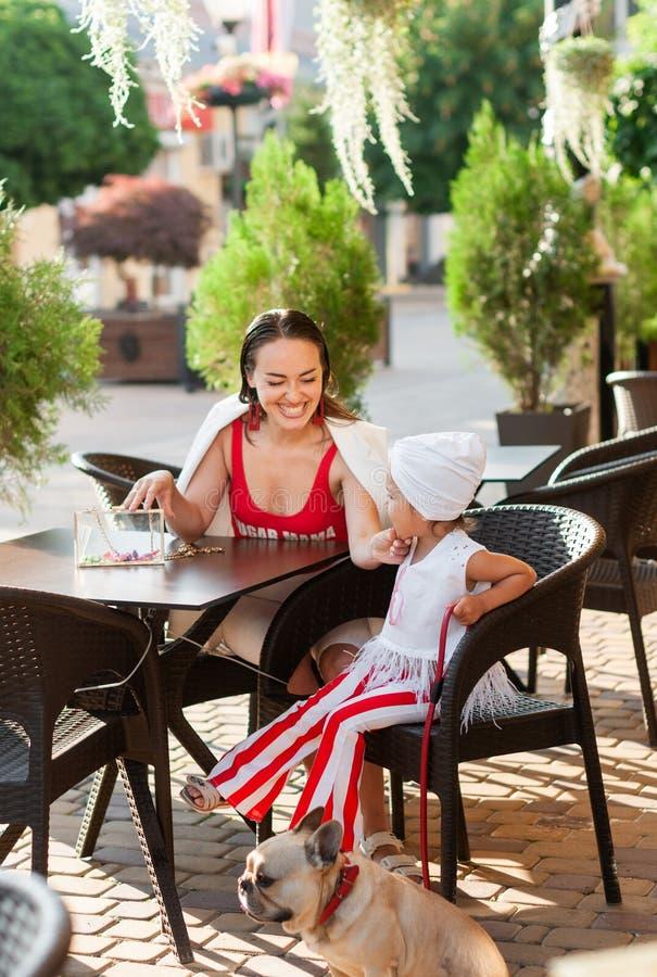 时髦的聊天在一个咖啡馆的母亲和女儿,与法国牛头犬 免版税库存照片